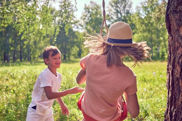 Kinderen spelen en lachen in de natuur. een jongen schudt een meisje in een schommel. lifestyle foto
