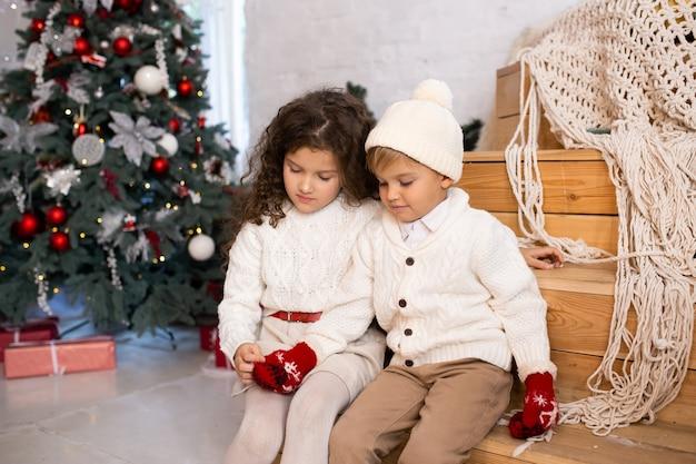 Kinderen spelen in de buurt van de kerstboom en lampjes op de achtergrond. prettige kerstdagen en fijne feestdagen.