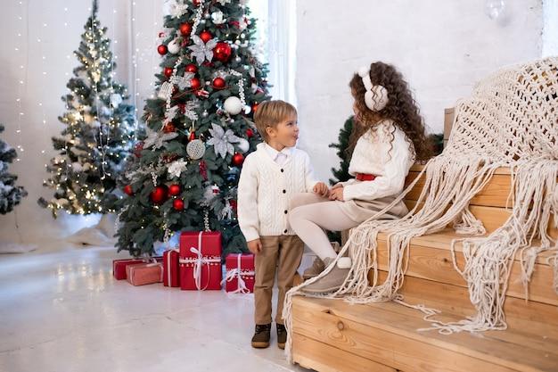 Kinderen spelen in de buurt van kerstboom en licht op de achtergrond. prettige kerstdagen en fijne feestdagen.