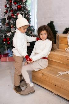 Kinderen spelen in de buurt van kerstboom en lichten