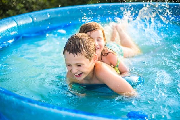 Kinderen spelen in de hete zomer met een bal in het zwembad. meisje en jongen . schattig klein meisje in zwembad buiten
