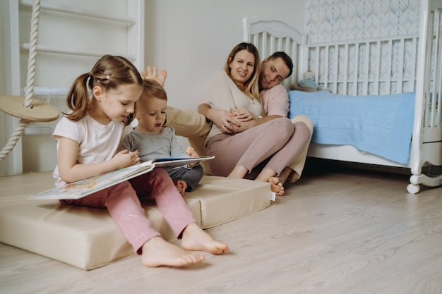 Kinderen spelen in de kinderkamer vader maakte een speelgoedpiramide meisje dat een boek leest