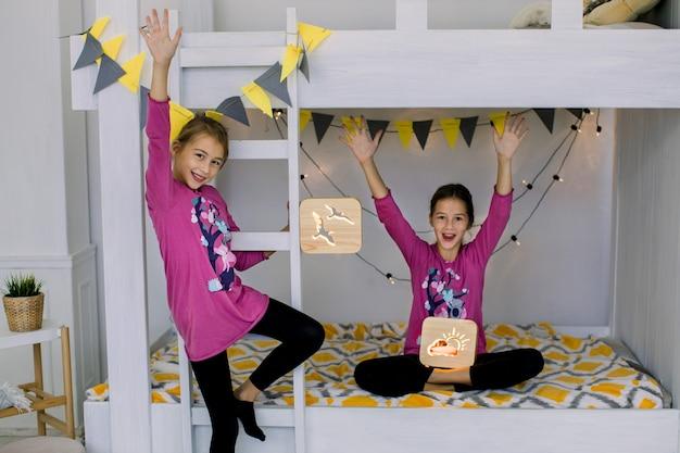 Kinderen spelen in de slaapkamer. twee grappige gelukkige meisjes 10 jaar oud, zusters in kleurrijke pyjama's, plezier op een stapelbed, met houten nachtlampjes.