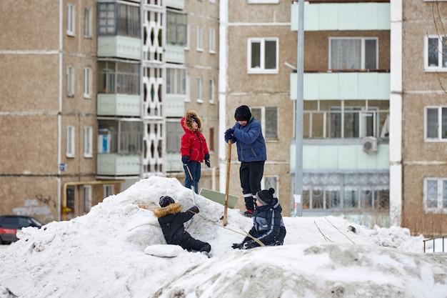 Kinderen spelen in de winter op een stapel vuile sneeuw. slechte ecologie