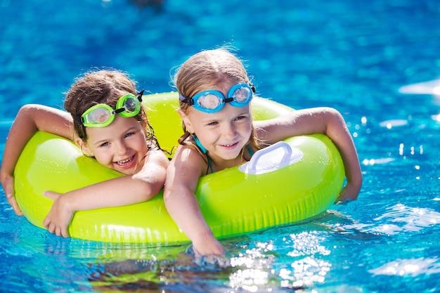 Kinderen spelen in het zwembad. twee kleine meisjes hebben plezier in het zwembad.