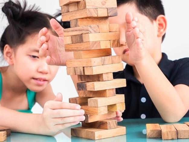 Kinderen spelen jenga, een torenspel met houtblokken