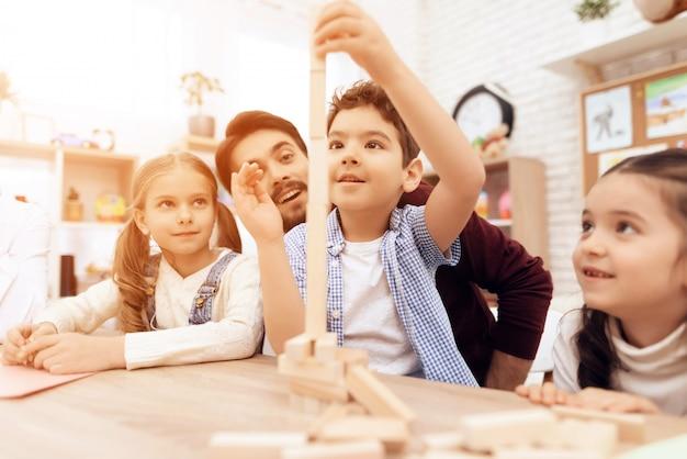 Kinderen spelen jenga met leraar in de klas