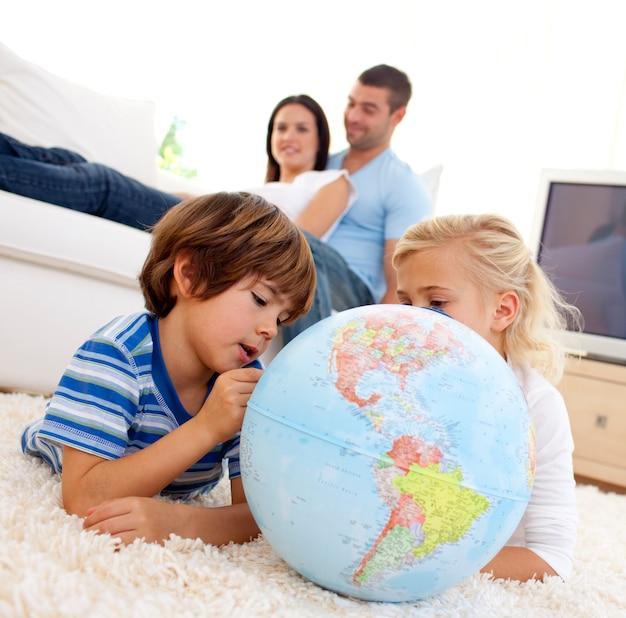 Kinderen spelen met een aardbol in de woonkamer