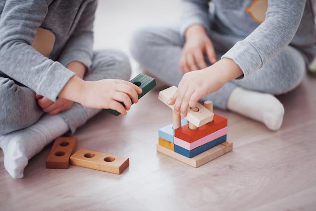 Kinderen spelen met een speelgoedontwerper op de vloer van de kinderkamer. twee kinderen spelen met kleurrijke blokken. educatieve spellen voor de kleuterschool. close-up bekijken.