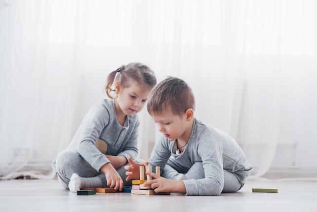 Kinderen spelen met een speelgoedontwerper op de vloer van de kinderkamer. twee kinderen spelen met kleurrijke blokken. educatieve spellen voor de kleuterschool