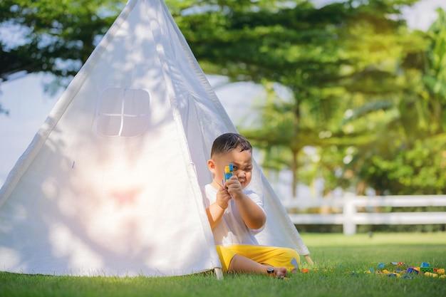 Kinderen spelen met kleurrijk speelgoed in een witte tent op speelplaats huis achtertuin