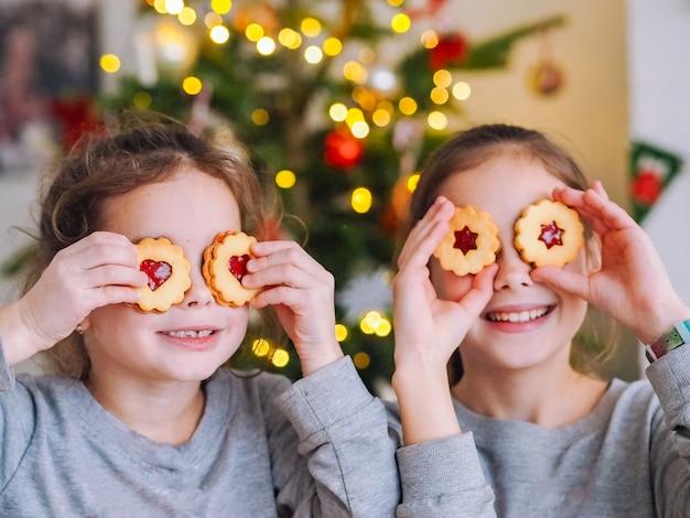 Kinderen spelen met koekjes onder de kerstboom in de kamer met kerstverlichting