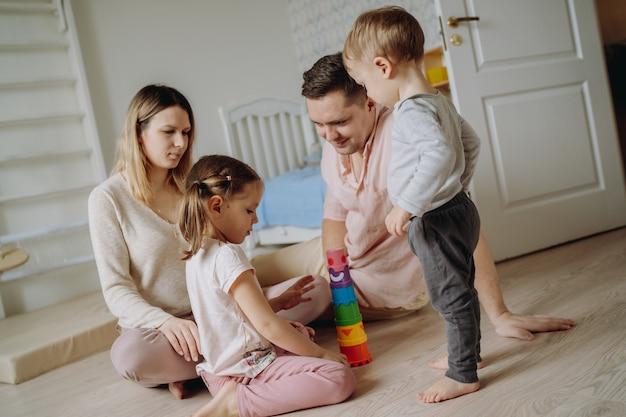 Kinderen spelen met ouders in kinderkamer vader maakte een speelgoedpiramide