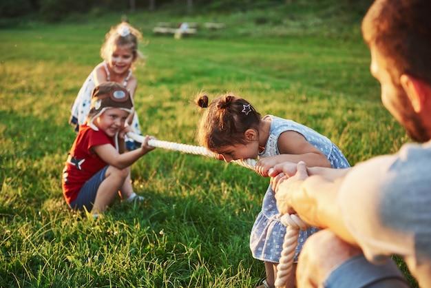 Kinderen spelen met papa in het park. ze trekken aan het touw en hebben plezier op een zonnige dag
