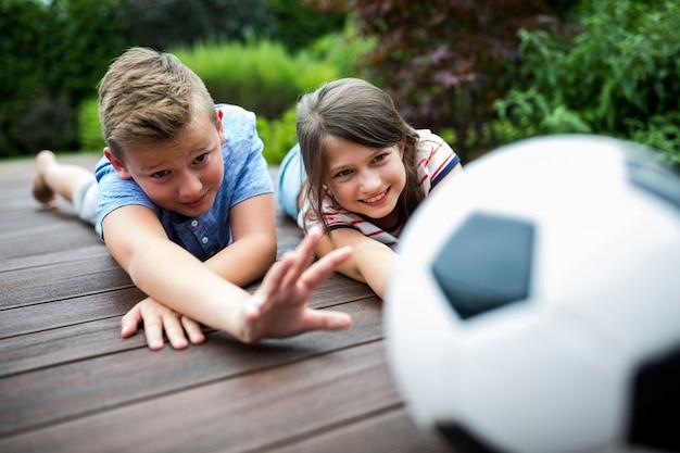 Kinderen spelen met voetbal op steiger
