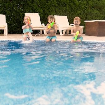 Kinderen spelen met waterkanonnen terwijl bij het zwembad