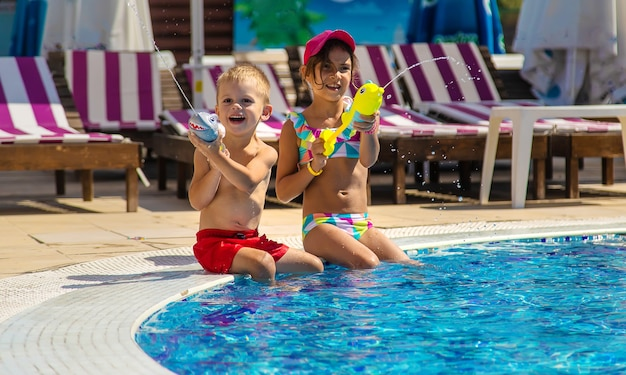 Kinderen spelen met waterpistolen in het zwembad. selectieve aandacht. water.