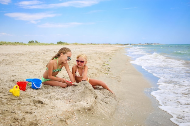 Kinderen spelen met zand op het strand.