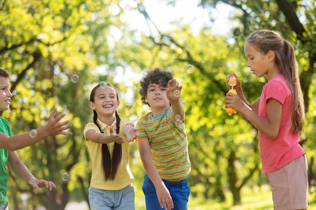 Kinderen spelen met zeepbellen in de natuur