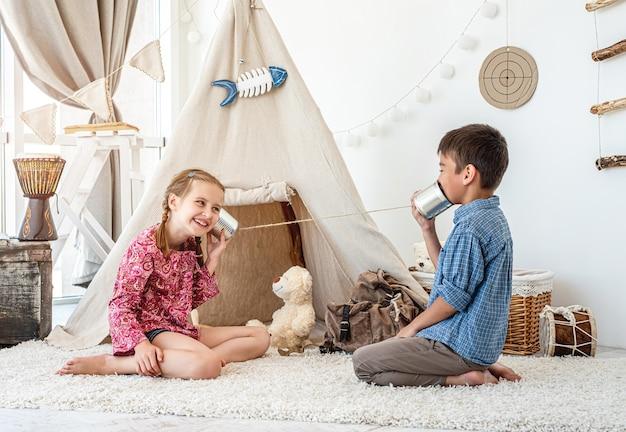Kinderen spelen met zelfgemaakte telefoon op wigwam oppervlak in lichte kamer