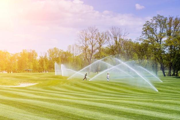 Kinderen spelen onder de stromen van watering station golfbanen