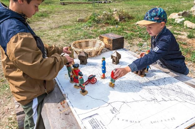 Kinderen spelen oorlog met houten figuren van soldaten op de oude kaart van rusland