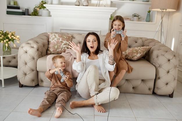 Kinderen spelen op de console met hun moeder. de vreugde van het passeren van een computerspel. moeder zoon en dochter strijden op de console