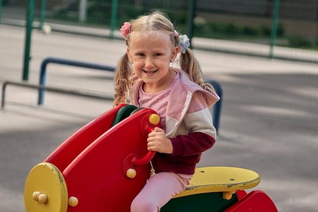 Kinderen spelen op de speelplaats. gelukkig lachend meisje veel plezier met slingeren en klimmen. buiten activiteit
