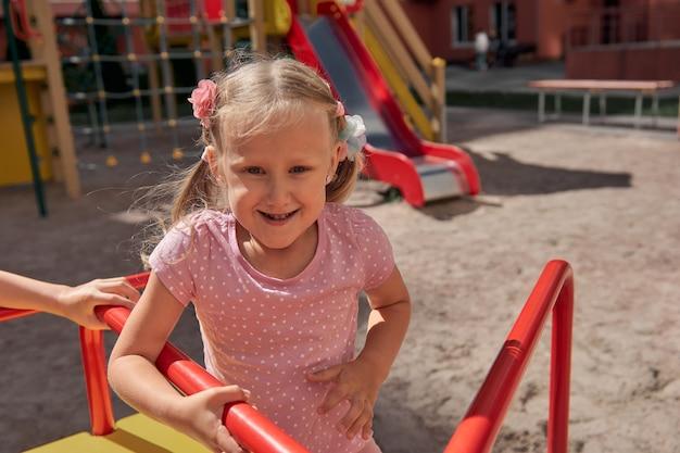 Kinderen spelen op de speelplaats. gelukkig lachende jongen en meisje veel plezier met slingeren en klimmen. buiten activiteit