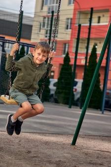Kinderen spelen op de speelplaats. gelukkig lachende jongen veel plezier met slingeren en klimmen. buiten activiteit