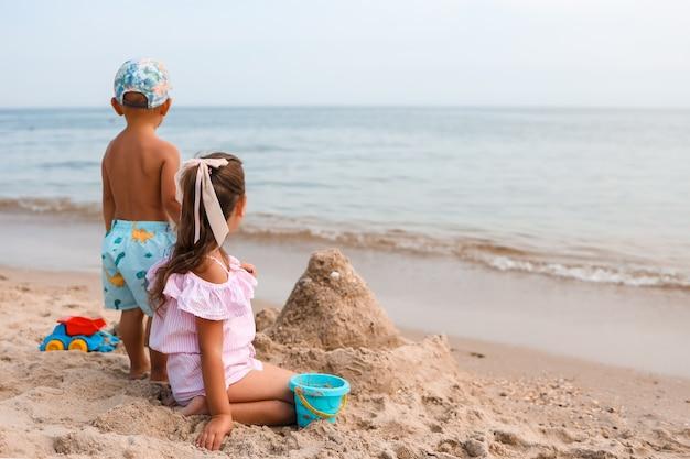 Kinderen spelen op een tropisch strand klein meisje graaft zand aan de kust familie zomervakantie