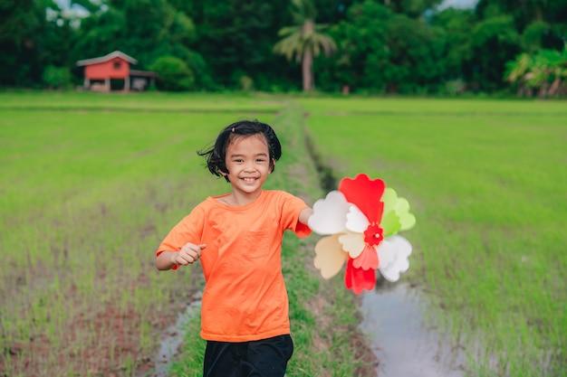 Kinderen spelen regenboog pinwheel of windmolen op blauwe lucht en wolken achtergrond prachtige natuur