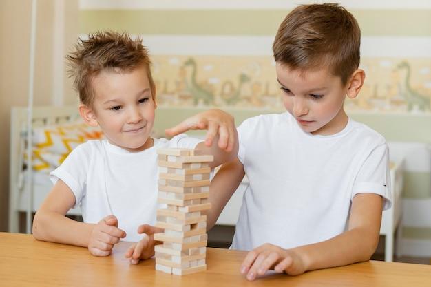 Kinderen spelen samen een houten torenspel