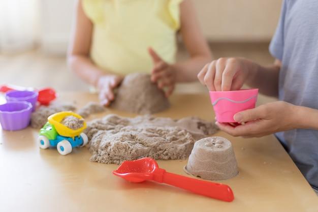 Kinderen spelen samen met kinetisch zand en zandvormen
