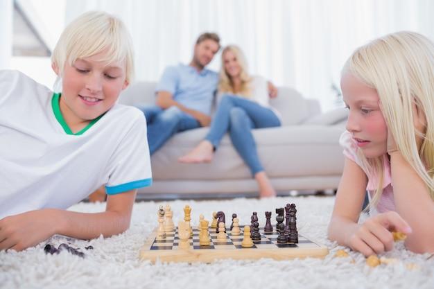 Kinderen spelen schaak in de woonkamer