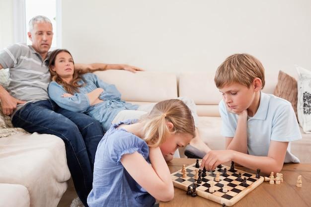 Kinderen spelen schaak voor hun ouders