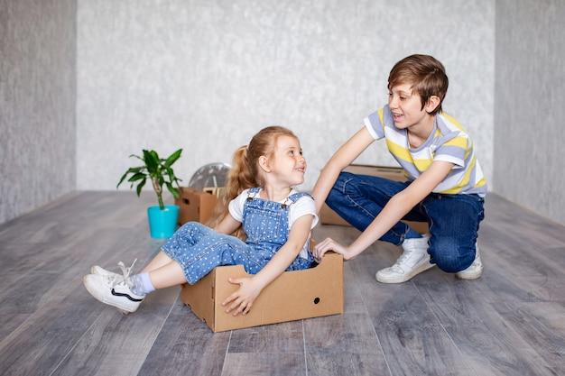 Kinderen spelen thuis met dozen in quarantaine in een nieuw appartement en spelen vrolijk zonder speelgoed.