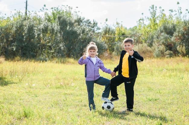 Kinderen spelen voetbal op het veld. gekleed in sportkleding