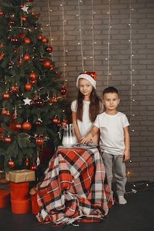 Kinderen staan in de buurt van de kerstboom. kinderen die koekjes met melk eten.