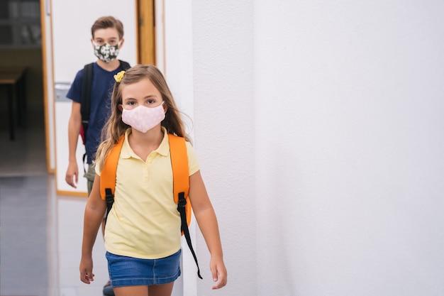 Kinderen student met maskers gaan naar de klas met behoud van sociale afstand. terug naar school tijdens de covid-pandemie
