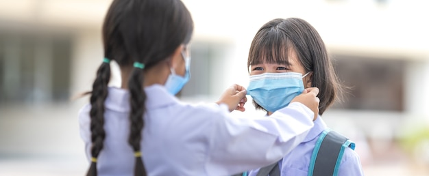 Kinderen studenten die een beschermend gezichtsmasker voor elkaar dragen om terug naar school te gaan