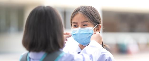 Kinderen studenten in studentenuniform dragen beschermend gezichtsmasker voor elkaar om naar school te gaan nadat de pandemische situatie van covid-19 beter wordt. terug naar school concept stock photo
