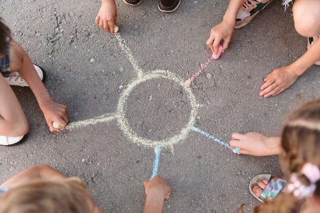 Kinderen tekenen een zon met krijt