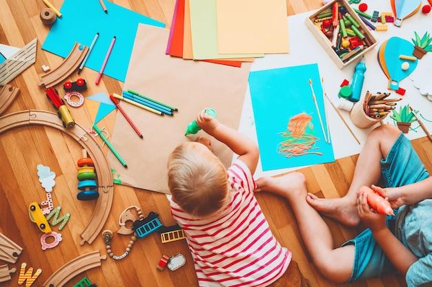 Kinderen tekenen en knutselen. kinderen met educatief speelgoed en schoolbenodigdheden voor creativiteit. achtergrond voor voorschoolse en kleuterschool of kunstlessen. jongen en meisje spelen thuis of in de kinderopvang