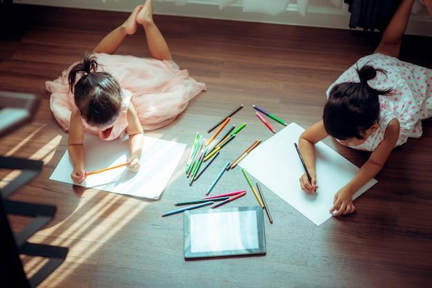 Kinderen tekenen op verdieping op papier. vintage kleur