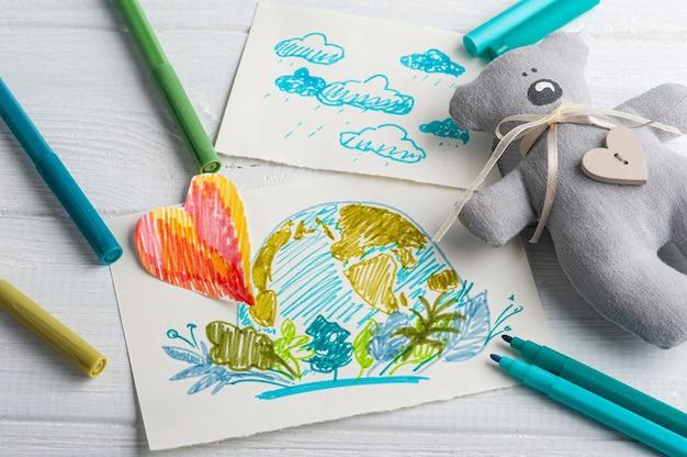 Kinderen tekenen van de aarde op witte tafel