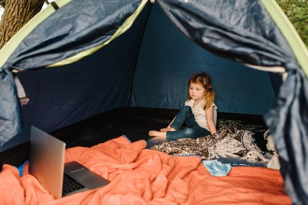 Kinderen toerisme. kind met behulp van laptop in de tent op de camping.