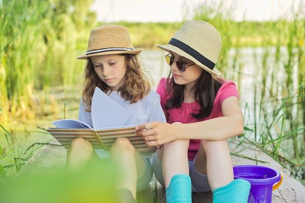 Kinderen, twee meisjes die rusten terwijl ze hun notitieboekje in de natuur lezen. kinderen zitten op houten meer pier, zomer zonsondergang water landschap achtergrond, landelijke stijl,