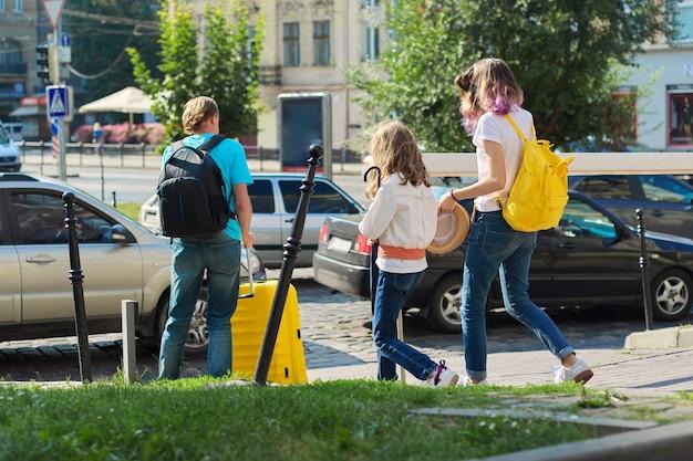 Kinderen, twee meisjes, dochters en vader, toeristen die door de stad lopen met rugzakken en een koffer. reizen, familie, vakantie, toerisme, zomerconcept