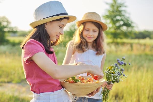 Kinderen twee meisjes op zonnige zomerdag in weiland met kom zoete kers, met zonsondergang